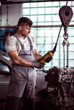 Automotive technician repairing engine. Image of automotive technician repairing broken engine Royalty Free Stock Photo