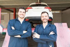 Automotive Workers Showing Contentment In Garage. Automotive workers showing contentment while standing in garage stock photo