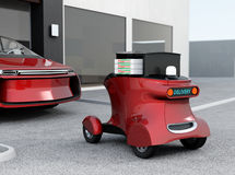 Autonomous delivery robot in front of the garage waiting for picking pizza Stock Image