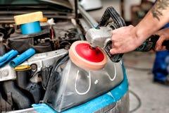 Autopflegekonzept mit einem Mechaniker, der die Scheinwerfer des Autos säubert Stockbilder