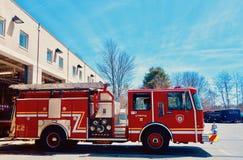 Autopompa antincendio rossa brillante che si muove dalla caserma dei pompieri, vista laterale immagini stock libere da diritti