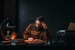 Autor barbudo en vidrios que lee un libro foto de archivo libre de regalías