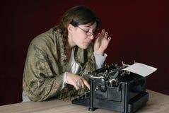 Autor de sexo femenino que pulsa en una máquina de escribir vieja imagen de archivo