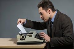 Autor joven feliz que mecanografía en la máquina de escribir Fotos de archivo