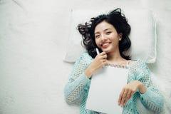 Autore, macchina da scrivere, donna di Intelligent del giornalista che si trova sul letto a fotografie stock libere da diritti