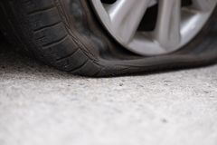 Autoreifenleck wegen des Nagelstampfens flacher Reifen auf Straße flatt lizenzfreie stockfotografie