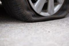 Autoreifenleck wegen des Nagelstampfens flacher Reifen auf Straße flatt stockfotografie