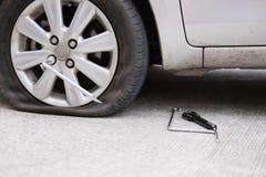Autoreifenleck wegen des Nagelstampfens flacher Reifen auf Straße flatt stockfotos