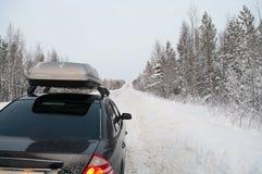 Autoreise in der schneebedeckten Straße des Winters Stockfotografie