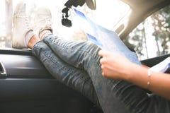 Autoreisender der jungen Frau mit Karte Stockfoto