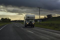 Autoreisewohnwagen, der auf Neuseeland-Asphaltstraße überschreitet Lizenzfreie Stockbilder