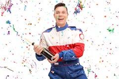 Autorennläufer, der Sieg mit einem Champagner feiert Lizenzfreie Stockbilder