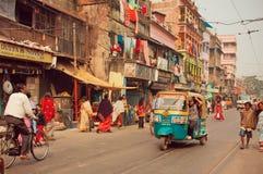 Autorickshaw nello stile indiano che guida tramite la via occupata della città Fotografia Stock