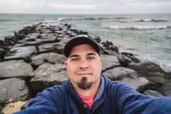 Autoritratto dell'uomo sul molo di pietra in oceano Fotografia Stock Libera da Diritti