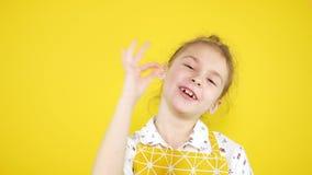 Autorización alegre de la muestra de la demostración de la chica joven sobre fondo amarillo almacen de video