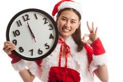 AUTORIZACIÓN asiática de la demostración de la muchacha de Santa Claus de la Navidad con el reloj en la medianoche Imagen de archivo libre de regalías