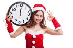 AUTORIZACIÓN asiática de la demostración de la muchacha de Santa Claus de la Navidad con el reloj en la medianoche Fotos de archivo