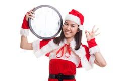 AUTORIZACIÓN asiática de la demostración de la muchacha de Santa Claus de la Navidad con el reloj en la medianoche Foto de archivo