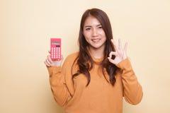 AUTORIZACIÓN asiática de la demostración de la mujer con la calculadora imágenes de archivo libres de regalías