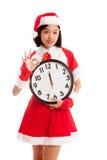 AUTORIZACIÓN asiática y reloj de la demostración de la muchacha de Santa Claus de la Navidad en la medianoche Fotografía de archivo