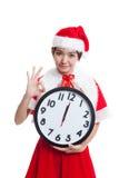 AUTORIZACIÓN asiática y reloj de la demostración de la muchacha de Santa Claus de la Navidad en la medianoche Imagenes de archivo