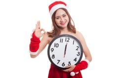 AUTORIZACIÓN asiática y reloj de la demostración de la muchacha de Santa Claus de la Navidad en la medianoche Fotos de archivo libres de regalías