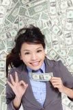 Autorización de la demostración de la mujer de negocios con la cama del dinero Imágenes de archivo libres de regalías