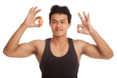 Autorización asiática muscular de la demostración del hombre con el huevo Foto de archivo libre de regalías
