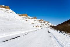 Autoroute d'hiver dans les montagnes par jour ensoleillé Images libres de droits