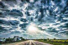 Autoroute par le paysage de pays avec les skyes et le Ra dramatiques du soleil Photographie stock