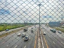Autoroute urbaine avec le chemin de palissade de beaucoup de voitures A Photo stock
