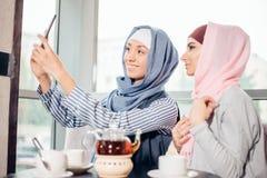 Autorretrato musulmán joven feliz de la toma de la mujer dos con handphone en el café Imagen de archivo libre de regalías
