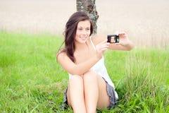 Autorretrato que toma adolescente lindo con las cámaras digitales Imagen de archivo libre de regalías