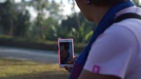Autorretratos maduros mismo de la mujer con el uso del smartphone móvil almacen de metraje de vídeo