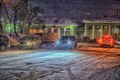 Autos auf der Straße nachts im Schnee Stockbild