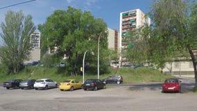 Autos auf Straßenüberquerung nahe einigen Bäumen stock footage