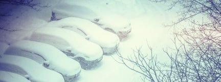 Autos bedeckt im Schnee auf einem Parkplatz im Wohngebiet DU Stockfotos