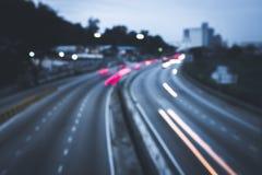 Autos beleuchten bei Sonnenuntergang auf der Straße zur Stadt Stockbild