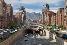 Autos, die durch Navvab-Tunnel von Teheran mit Milad Tower im Hintergrund überschreiten Lizenzfreies Stockfoto