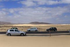 Autos, die entlang der Straße in der Wüste stehen Stockbild