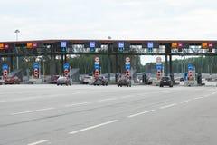Autos, die Mautstraßeeintrittsstift von einer Landstraße aproaching sind stockbild