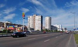 Autos fahren entlang die Pflasterung von Kiew, auf der es Shops und Apartmenthäuser gibt Lizenzfreies Stockbild