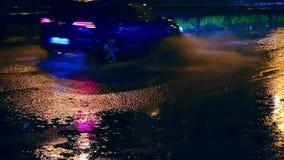 Autos fahren in große Pfützen auf der Nachtstraße in der Stadt, Spraypfützen zerstreuen von unterhalb der Wagenräder stock footage