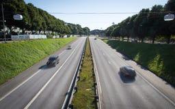 Autos, laufend in eine Schweden-Autobahn Lizenzfreie Stockfotos