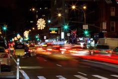 Autos mit den unscharfen Lichtern, die auf NYE in NYC unter Weihnachten O fahren stockbild