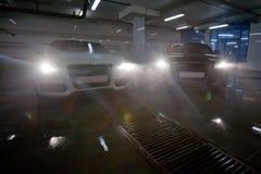 Autos mit Scheinwerfer in der Waschanlage Stockfotos