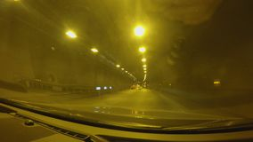 Autos rushing through illuminated tunnel, long trip by car, road infrastructure. Stock footage stock footage