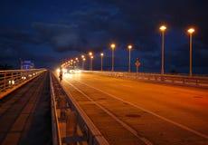Autos und ein Fahrradreiter reisen in der Dämmerung auf die 17. Straßen-Dammbrücke im Fort Lauderdale, Florida Lizenzfreies Stockbild