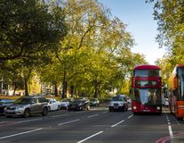 Autos und rote Busse, die durch die Straßen nahe Hyde Park in London überschreiten Lizenzfreie Stockbilder