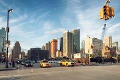 Autos und Taxi, die den Schnitt von 34. St. und von 11. entlang der Baustelle von 3 Hudson Boulevard kreuzen Stockfotografie